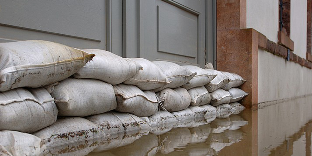 Sand bags preventing water from seeping under a doorway